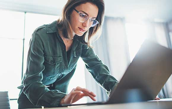Lady wearing glasses while working on a laptop