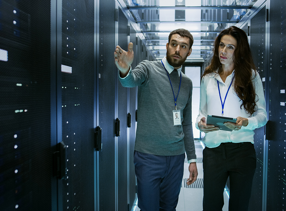 Man and woman pointing in a server room